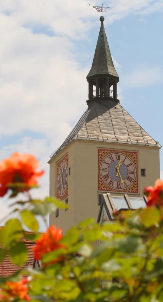 Blick durch Blumen hindurch zum Turm des Alten Rathauses in Deggendorf mit der Rathausuhr