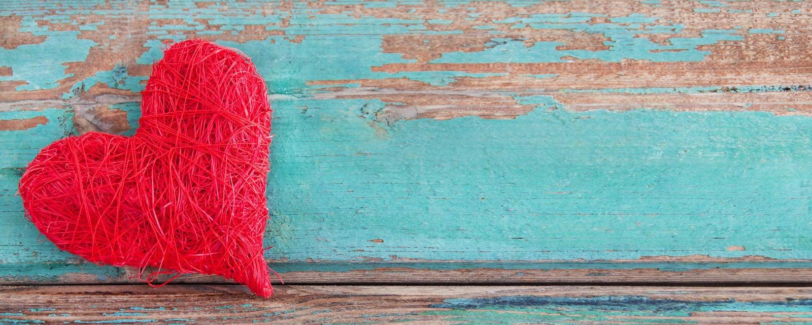 Rotes Stoffherz auf lackierten Holz, wo die minte Farbe schon abblättert