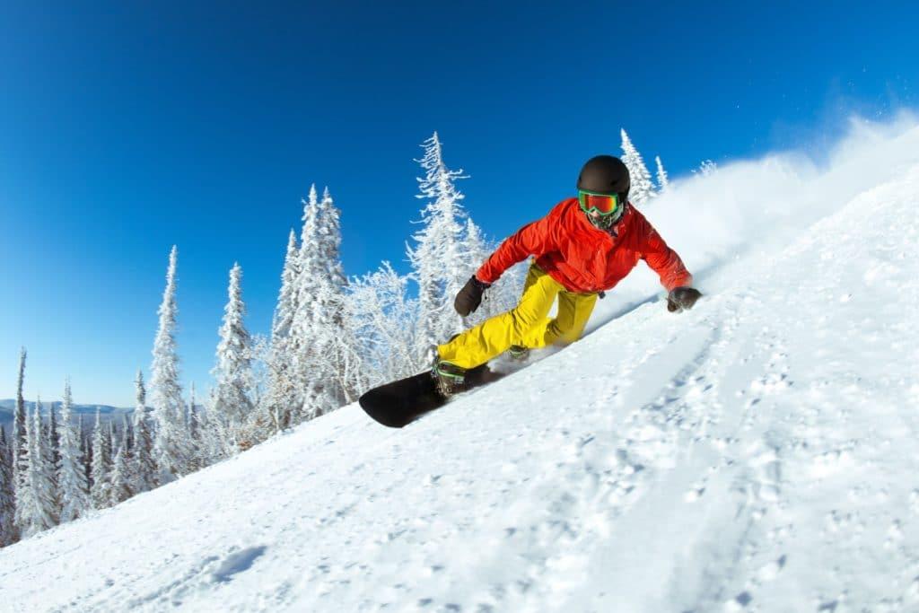 Snowboarder auf dem Weg die Piste runter
