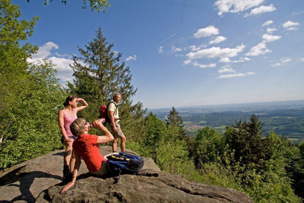 Eine Gruppe Menschen sitz auf einem Felsen und schauen ins Tal