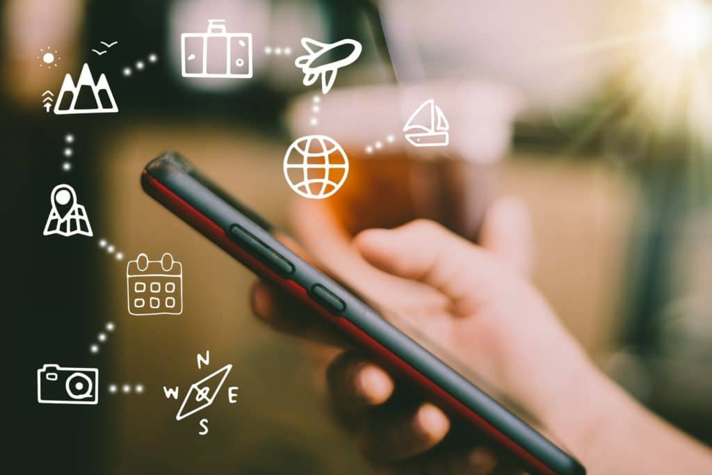 Handy mit vielein virtuellen Icons die verdeutlichen, dass nach einer Unterkunft gesucht wird