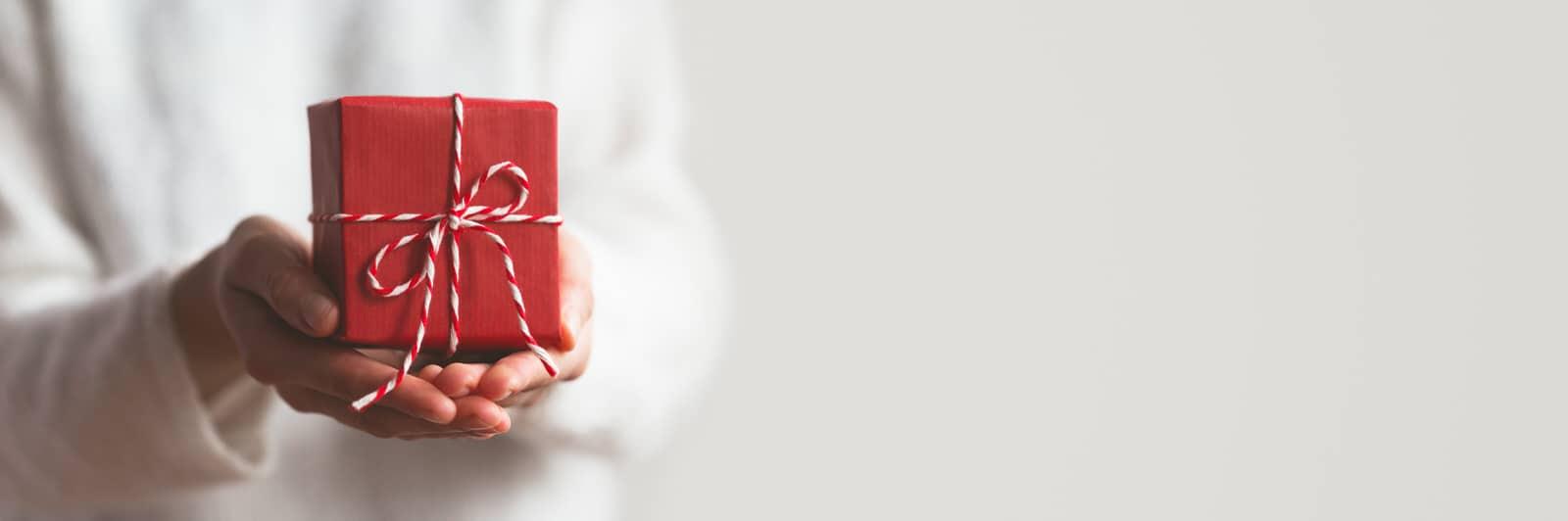 Eine Frau hält ein verpacktes Geschenk in der Hand und überreicht es
