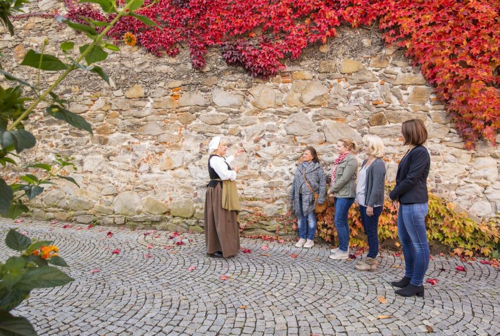 Die Knödelwerferin steht vor der historischen Alstadt-Mauer in Deggendorf, wo ihr vier Teilnehmer einer Stadtführung genau zuhören