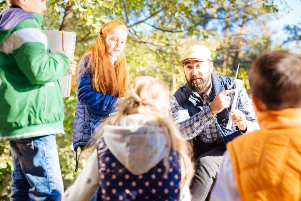 Eine männliche Person erklärt und zeigt Kindern etwas in der Stadt
