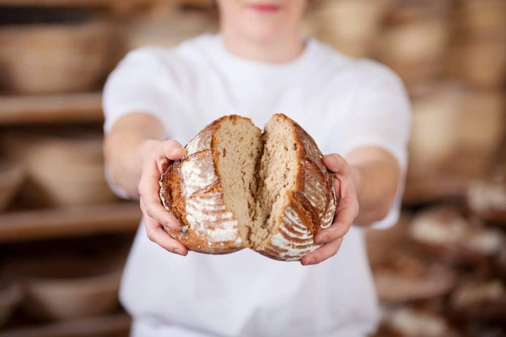 Bäcker zeigt frisch gebackenes Brot